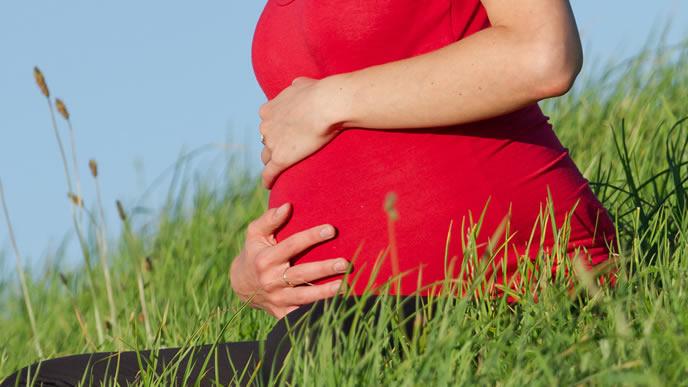 お腹の胎動を両手で感じる妊婦さん