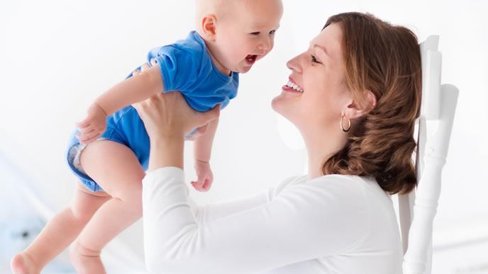 高い高いして赤ちゃんをあやすママ
