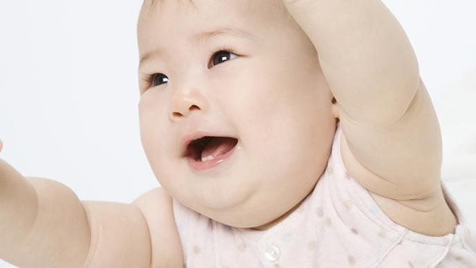 ママに抱っこをせがむ赤ちゃん