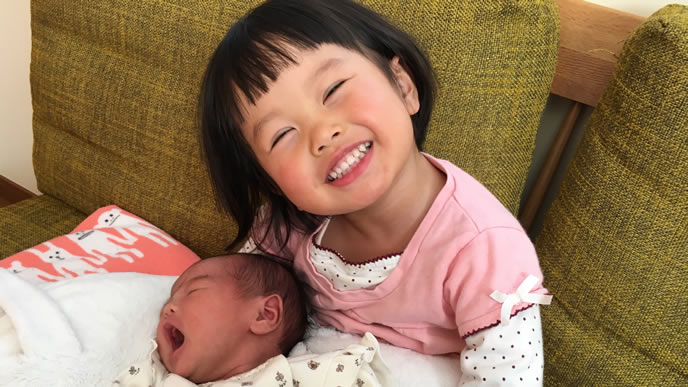 生まれてきた妹を抱っこする姉