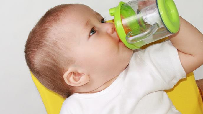 ベビーマグで水分を摂る赤ちゃん