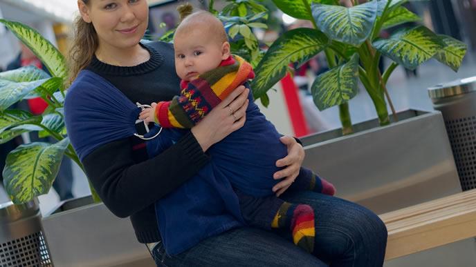 赤ちゃんを抱っこして買い物にくるママ