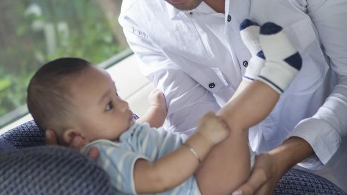 赤ちゃんをチャイルドシートに乗せるパパ