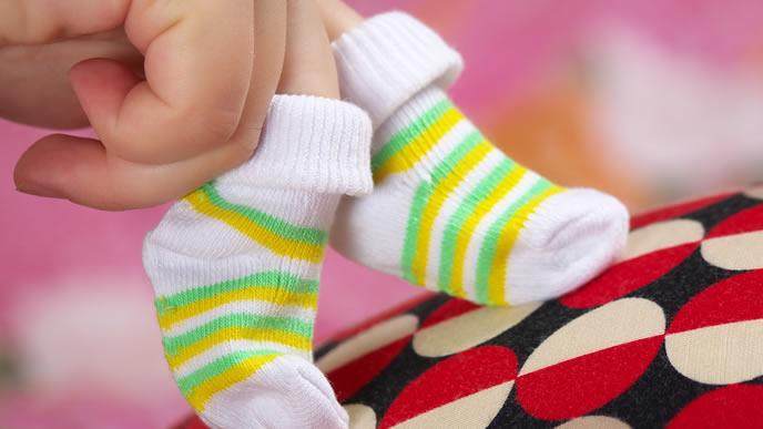 赤ちゃんの靴下を買い出産準備をするママ