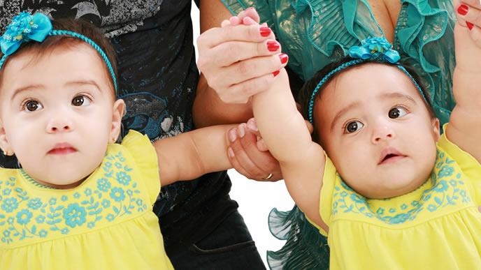 バンザイをした可愛い双子の赤ちゃん
