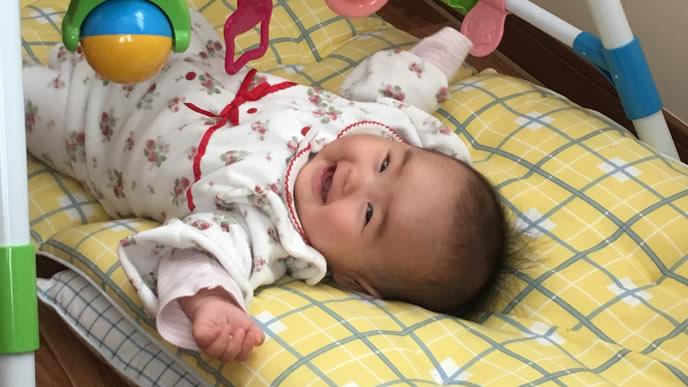 笑顔でママをみる赤ちゃん
