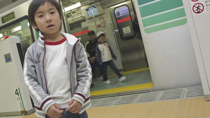 電車の前で立ち止まる男の子