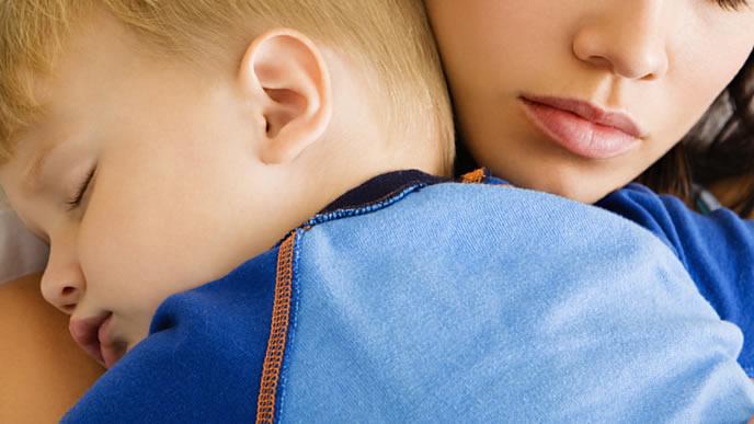 ママに抱っこされて安心して眠る赤ちゃん