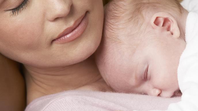 ママの胸でスヤスヤ眠る新生児の赤ちゃん