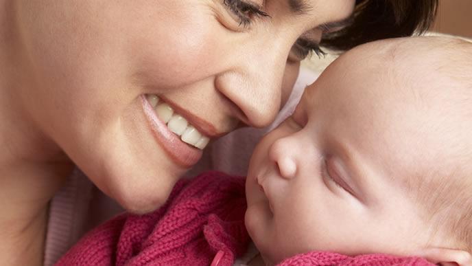 赤ちゃんに微笑みかけるママ