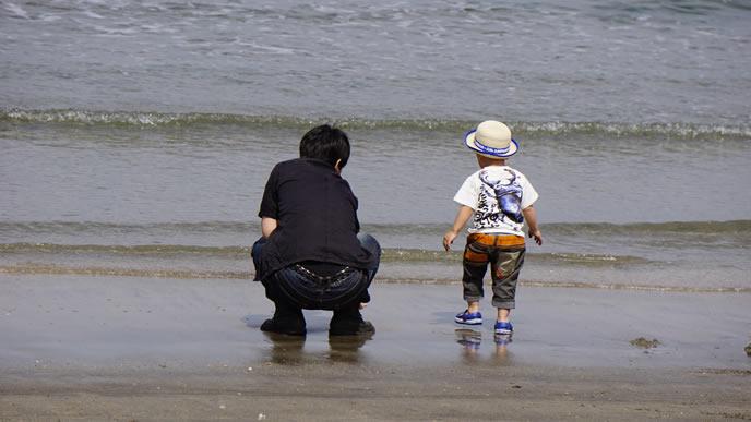パパと二人で海岸を歩く男の子