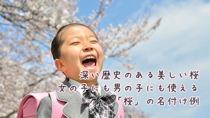 桜の花をバックに記念写真をとる小学生