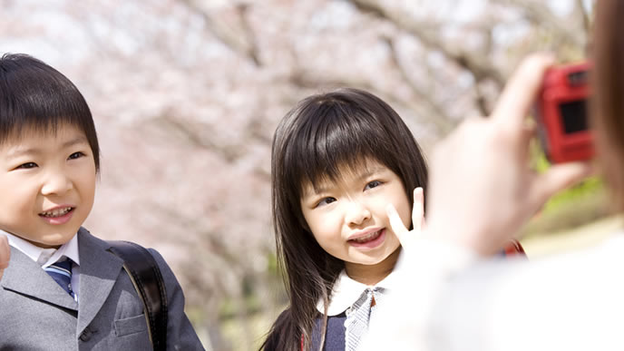 兄妹の写真を桜の木と共に写真に撮るママ