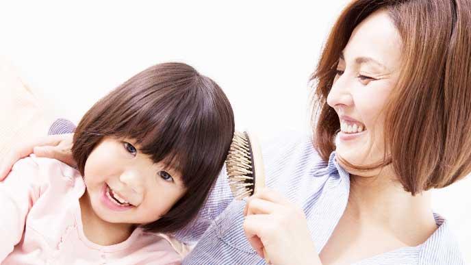 子供の髪をブラシで梳かしてスキンシップをしている母親