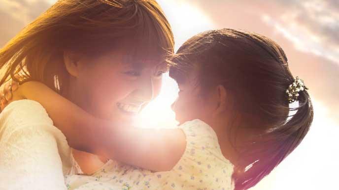 母親に抱き上げられて笑顔の女の子