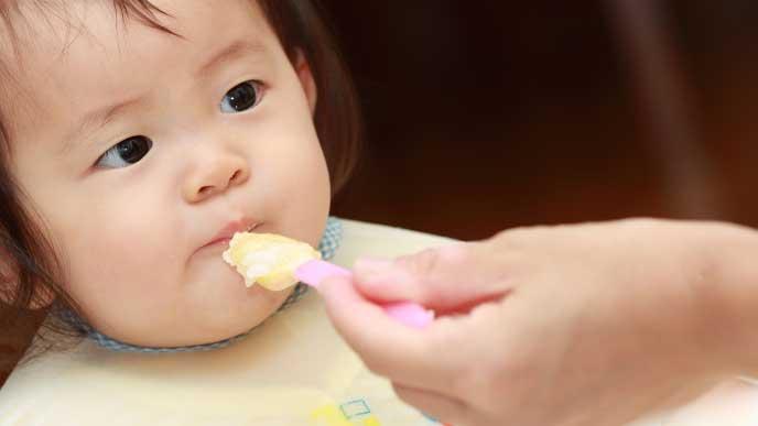 スプーンに乗った離乳食を口を閉じて食べようとしない赤ちゃん