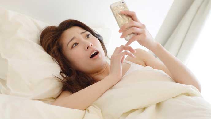 ベッドの中で時間を見てビックリしている寝坊した母親