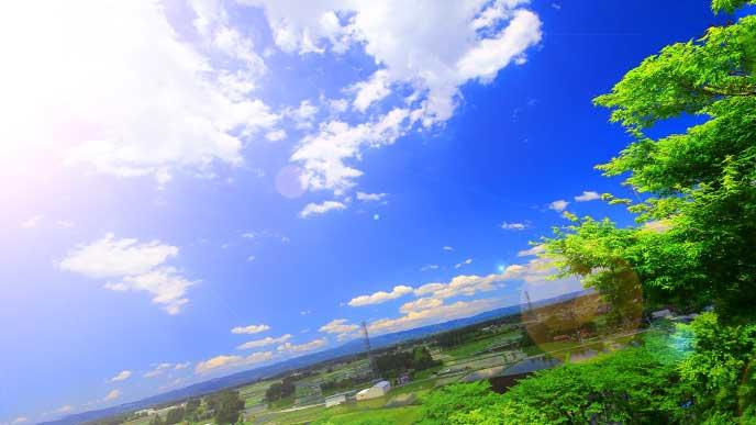 晴れた日に太陽に照らされた丘から見た街並み