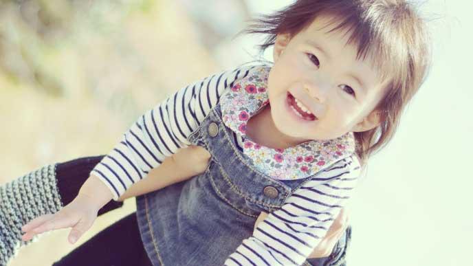 母親に高い高いしてもらって笑顔の女の子