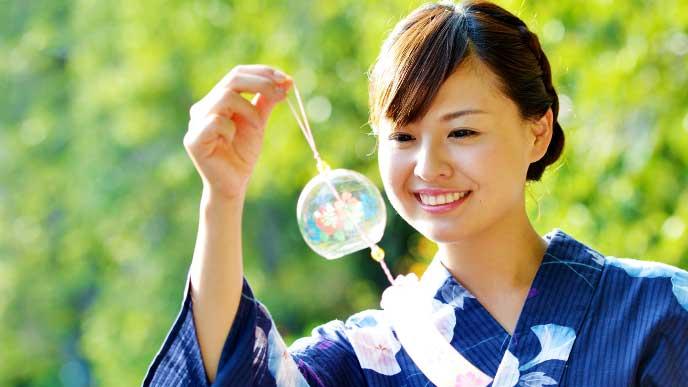 風鈴を手に持っている浴衣を着た若い女性