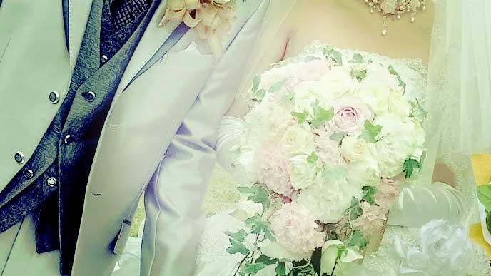 ウェディングドレスを着て新郎と腕を組んでいる花嫁