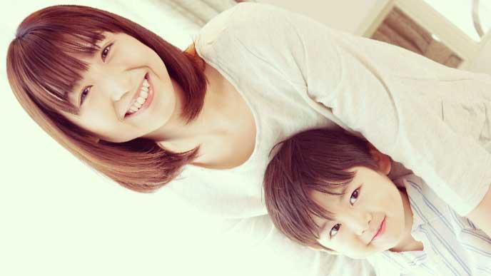 母親に後ろから抱っこされている男の子