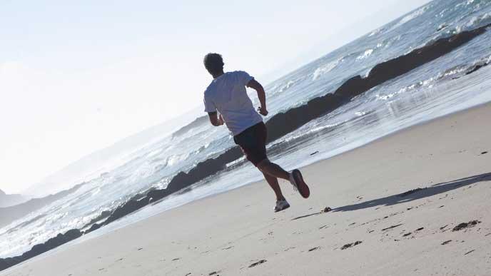 砂浜を走っている男性
