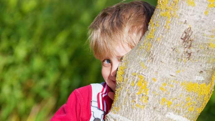 恥ずかしくて木の陰に隠れている男の子