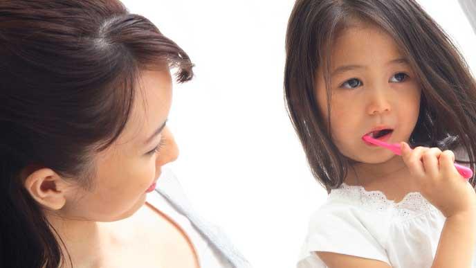 子供の歯磨きを手伝っている母親