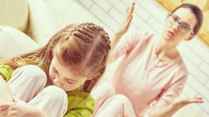 母親に叱られて体育座りをして落ち込んでいる女の子