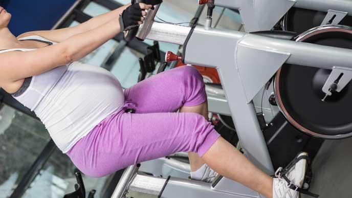運動用のバイクマシンに乗っている妊婦さん