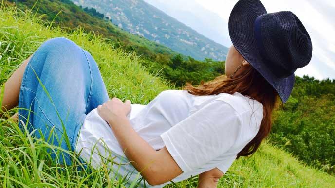 散歩の途中で草むらに座って休んでいる妊婦さん