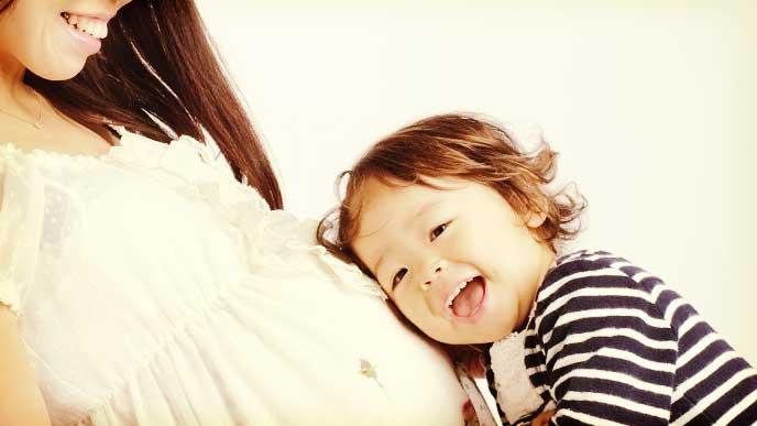 妊娠しているママの大きなお腹に耳を付けて音を聞いている小さな女の子