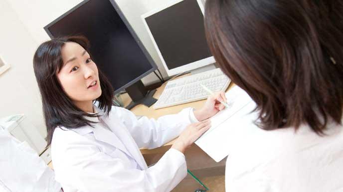 病院で産婦人科女医に母性健康管理指導事項連絡カードを書いてもらっている妊婦さん