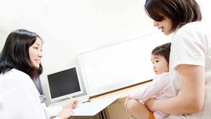 病院で女医に水いぼの症状を診てもらっているママに抱っこされてる女の子