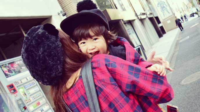 母親に抱っこされながら散歩している笑顔の女の子