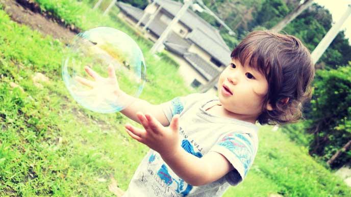 家の前でシャボン玉で遊んでいる男の子
