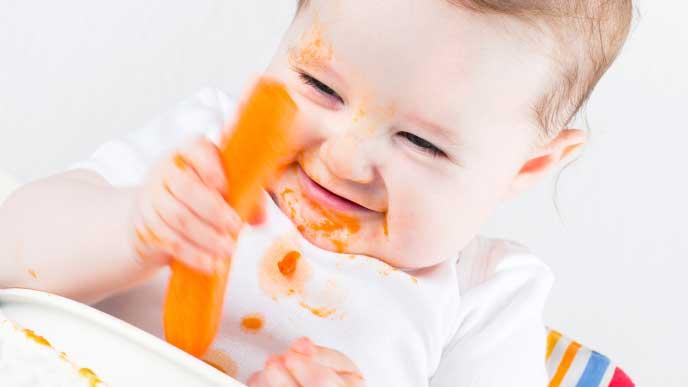 野菜スティックを手づかみで食べてる赤ちゃん