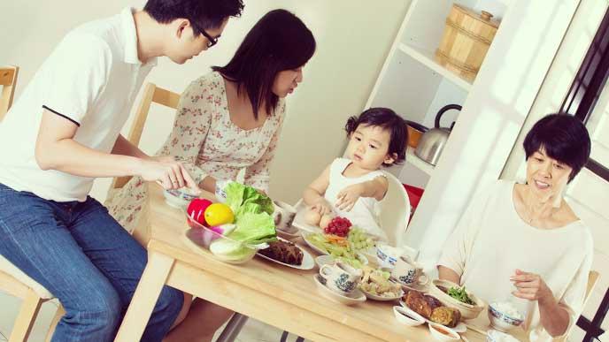 家族と一緒の食卓で離乳食を食べてる赤ちゃん
