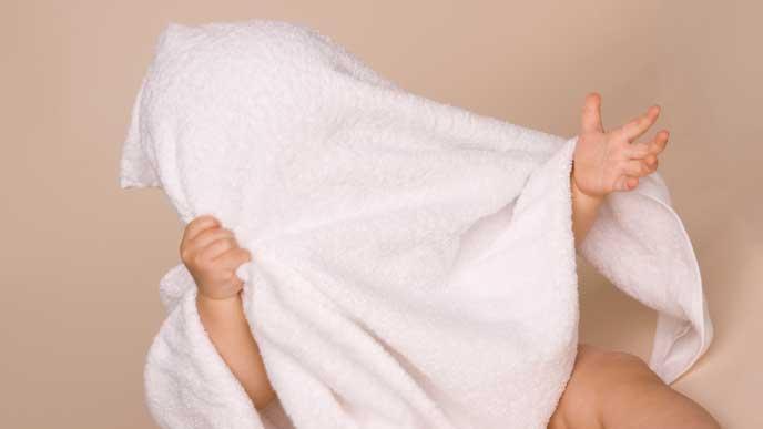タオルを頭からかぶってる赤ちゃん