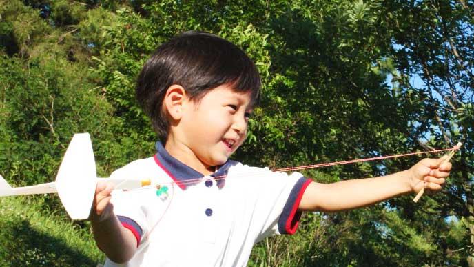 紙飛行機を飛ばそうとしている男の子