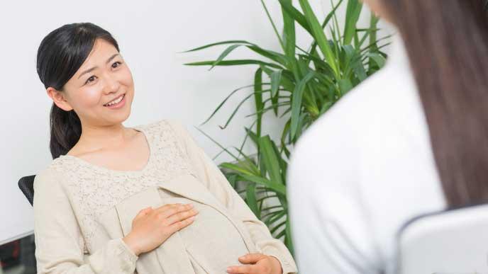病院で限度額適応認定証について聞いている妊婦さん
