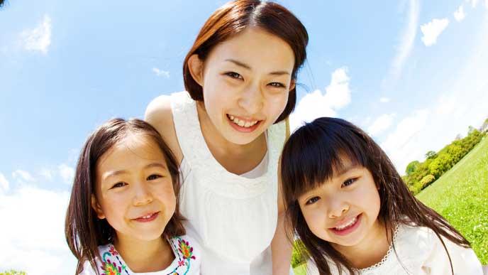笑顔の二人姉妹と母親