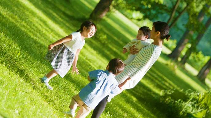 公園を散歩してる3人兄妹とママ