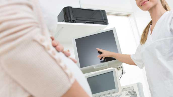 女性医師から妊婦健診の説明を受けている妊婦さん