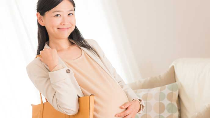 ワンピースを着て大きなトートバックを持って妊婦健診に行こうとしている妊婦さん
