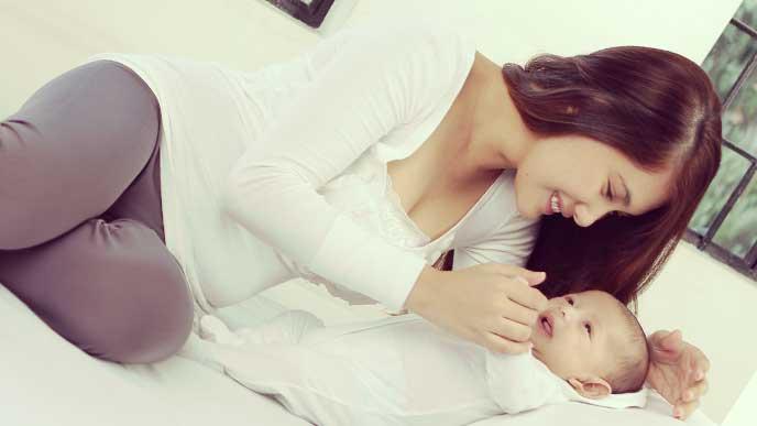 覆いかぶさって赤ちゃんの顔を見てる母親