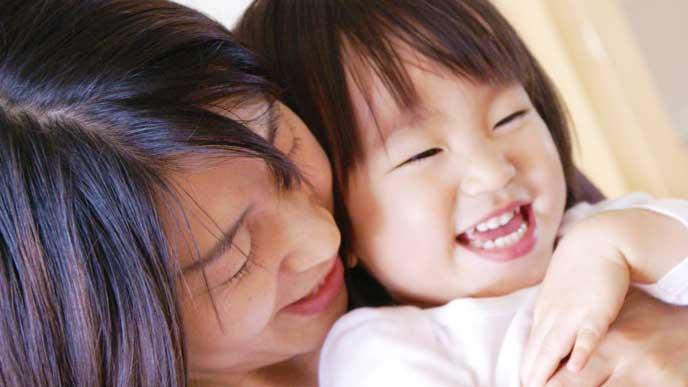 赤ちゃんを後ろから抱っこしている母親