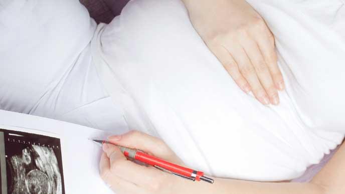 エコー写真を見ながらバースプランをノートに書いてる妊婦さん