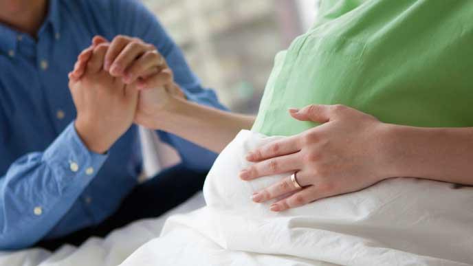病院で陣痛が始まった妊婦さんの手を握っている旦那さん